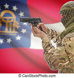 Male in muslim keffiyeh with gun in hand and flag on background - Georgia