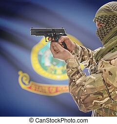Male in muslim keffiyeh with gun in hand and flag on background - Idaho