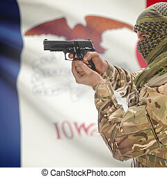 Male in muslim keffiyeh with gun in hand and flag on background - Iowa