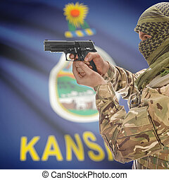Male in muslim keffiyeh with gun in hand and flag on background - Kansas