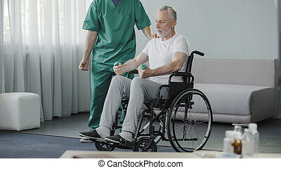 Male in wheelchair pumping his weak muscles with help of nurse, rehabilitation