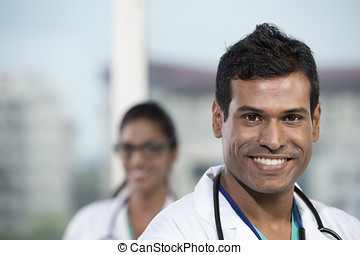 Male Indian doctor standing with his colleague