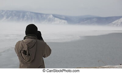 Male Indian tourist shoots snow-capped mountains on lake....