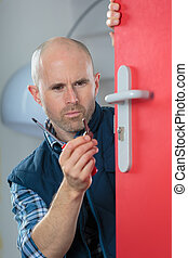male installing door lock on door