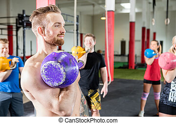 Male Instructor Lifting Kettlebell With Clients In Gym