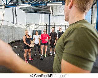 Male Instructor Training Athletes At Gym
