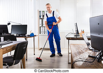Male Janitor Cleaning Floor With Broom