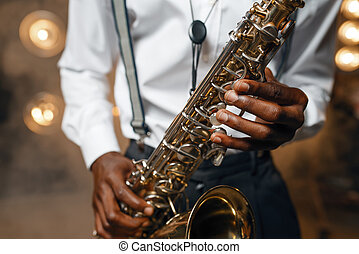 Male jazz performer plays the saxophone on the stage with spotlights. Black jazzman preforming on the scene