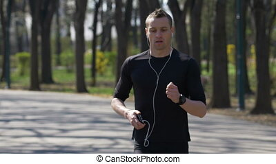 Male jogger running in park listening music stopping to check smartphone and smartwatch trackers