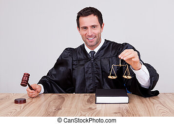 Male Judge Holding Gavel and Scale In Courtroom