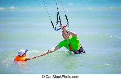 Male kite surfer helping young boy to come closer