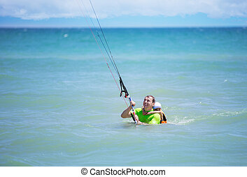 Male kite surfer showing young boy how to ride kite