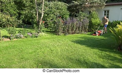 male landscaper man mowing lawn in the yard of his homestead...