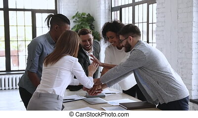 Successful male leader unite happy multiracial team people stack hands on table together promising support trust in partnership, help in collaboration, professional leadership concept, slow motion