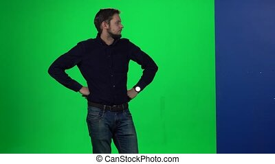 Male leaning his hand on wall standing against green, screen...