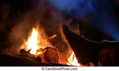 Male leg warming by the campfire into the night forest