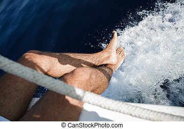 Male legs against background of sea water