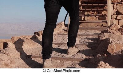 Male legs climbing up on desert stairs. Slow motion. Man...