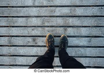 Male legs in boots on frozen wooden planks