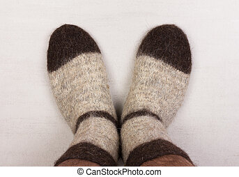 male legs in gray knitted socks made of dog hair close-up, top view