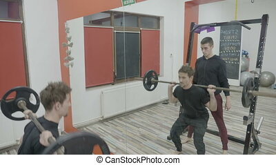 Male lifting weights and doing squats to work out his body muscles in gym with the help of a personal trainer