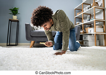 Male Looking At Carpet With Magnifying Glass
