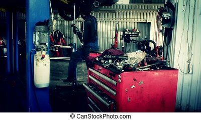 male maintenance engineer arranging tools in drawer at car workshop