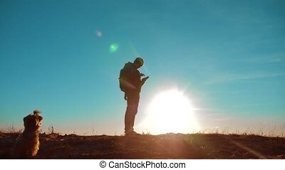Male man and dog worth it tourist with backpack smartphone navigation sunlight stands on top of mountain. slow motion video. man and dog silhouette at sunset. hikers adventure and the go walking. travel silhouette mountains lifestyle