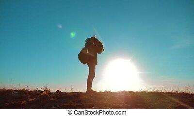 male man silhouette traveler raises the little Yorkshire...