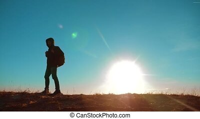 Male man walking lifestyle worth it tourist with backpack sunlight adventure stands on top of mountain . slow motion video. man silhouette at sunset . hikers adventure and the go . travel silhouette mountains
