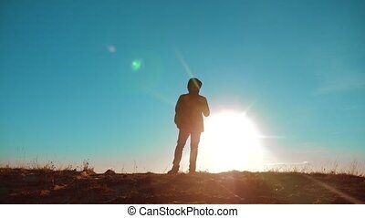 Male man worth it tourist with backpack smartphone navigation sunlight stands on top of mountain. slow motion lifestyle video. man silhouette at sunset . hikers adventure and the go walking. travel silhouette mountains