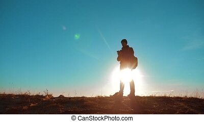 Male man worth it tourist with backpack smartphone navigation sunlight stands on top of mountain. slow motion video. man silhouette at sunset. hikers adventure lifestyle and the go walking. travel silhouette mountains