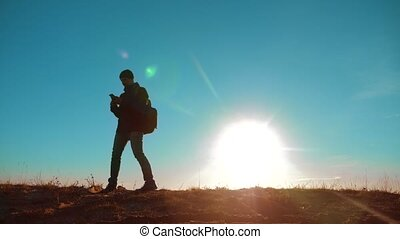 Male man worth it tourist with backpack smartphone navigation sunlight stands on top of mountain. slow motion video. man silhouette at sunset. lifestyle hikers adventure and the go walking. travel silhouette mountains