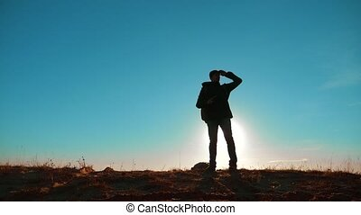 Male man worth it tourist with backpack smartphone navigation sunlight stands on top of mountain. slow motion video. man silhouette at sunset. hikers adventure and lifestyle the go walking. travel silhouette mountains