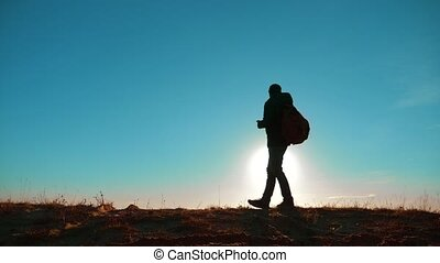 Male man worth it tourist with backpack smartphone navigation sunlight stands on top of mountain. slow motion video. man silhouette at sunset. hikers adventure and the go walking lifestyle . travel silhouette mountains