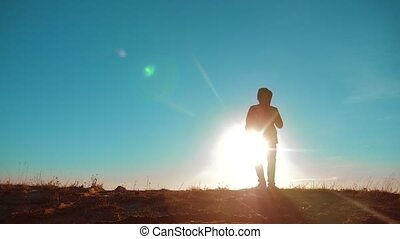 Male man worth it tourist with backpack smartphone navigation sunlight stands on top of mountain. lifestyle slow motion video. man silhouette at sunset . hikers adventure and the go walking. travel silhouette mountains
