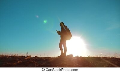 Male man worth it tourist with backpack smartphone navigation sunlight stands on top of mountain. slow motion video. man silhouette at sunset. hikers lifestyle adventure and the go walking. travel silhouette mountains