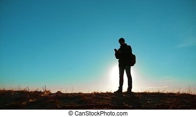 Male man worth it tourist with backpack smartphone navigation sunlight with dog stands on top of mountain. slow motion video. man silhouette at sunset. hikers adventure and the dog go walking. travel mountains silhouette lifestyle