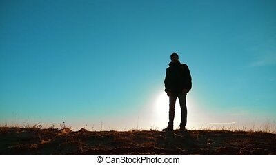 Male man worth it tourist with backpack with dog stands on top of a mountain. man silhouette at sunset. hikers adventure and dog go walking. travel mountains silhouette lifestyle