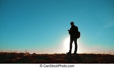 Male man worth it tourist with backpack with dog stands on top of mountain. slow motion video. man silhouette at sunset. hikers adventure and the dog go walking. travel mountains lifestyle silhouette