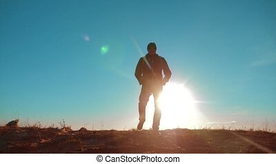 Male man worth it tourist with dog stands on top of mountain. man silhouette at sunset. hikers adventure and the dog go walking. travel mountains lifestyle silhouette