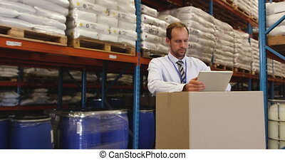 Male manager using tablet in warehouse 4k - Middle aged ...
