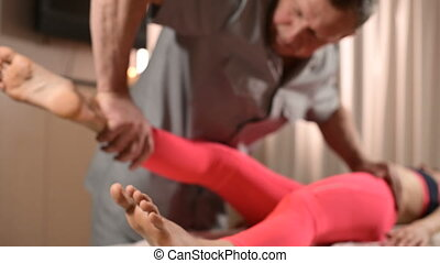 Male manual visceral therapist masseur treats a young female...