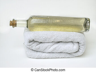 bottle of corked natural massage oil on white bath towel on plain white background