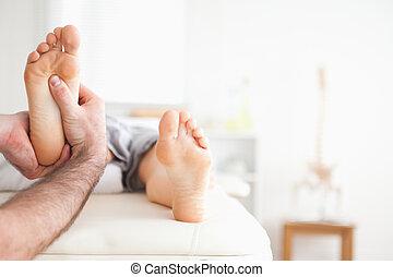 Male masseur doing a reflexology massage