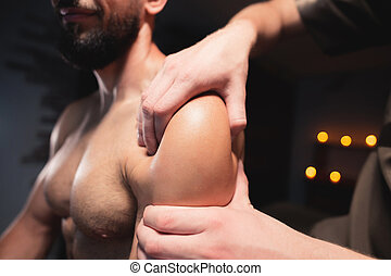 Male masseur doing sports massage in luxury spa salon to male athlete with a beard on the background of burning candles