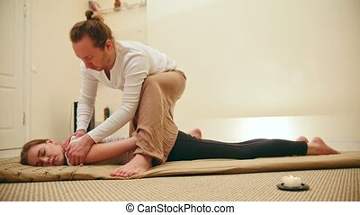 Male masseur holds the thai massage session - flexing the ribs and spine, slider