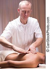 Male masseur massaging woman