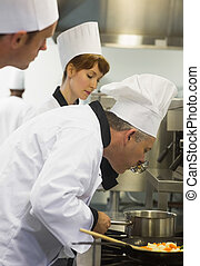 Male mature chef tasting some food in the kitchen