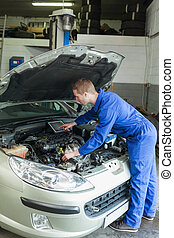 Male mechanic analyzing car engine - Male mechanic with...